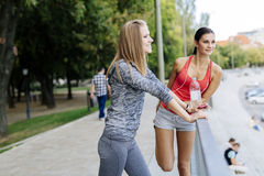 Two women stretching before jogging Royalty Free Stock Photo