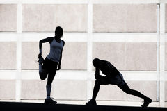 Two women stretching before running. Royalty Free Stock Photo