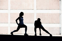 Two women stretching before running. stock photo