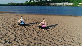 Two women stretching yoga on the sandy beach of the river. Beautiful city view. stock video
