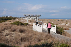 Two women stroll across a bridge in the dunes to a wooden archway to a roadway Stock Images
