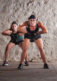 Two Women Struggle with Boot Camp Workout. Struggling young white women sweating and lifting weights Royalty Free Stock Images