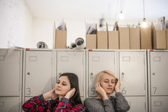 Two women students think on the background of the closed lockers Royalty Free Stock Photography