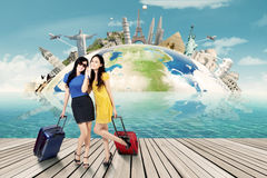 Two women with suitcase and the world landmark Royalty Free Stock Images