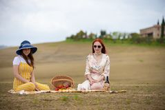 Two women in summer clothes sitting on the blanket and having a picnic stock photography