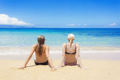 Two women sun tanning on a sunny beautiful beach Royalty Free Stock Photos