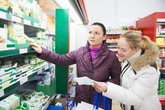 Two women at supermarket dairy shopping Royalty Free Stock Images