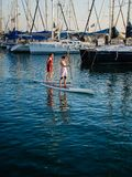 Two women surfing on sups in Tel Aviv port in front of harbored boats and yachts royalty free stock images
