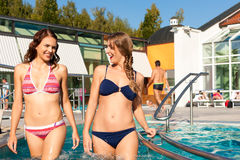 Two women in swimming pool. Two happy young women wading water in hydrotherapy in a health spa Royalty Free Stock Photo