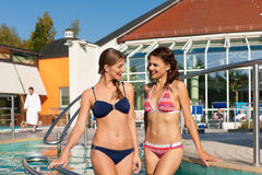 Two women in swimming pool. Two happy young women walking into the water of a swimming pool; they are wearing a bikini Stock Images