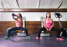 Two women swinging kettle bell parallel squat. Gym Royalty Free Stock Photos