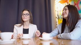 Two women at table listen, smile and drink a beverage from white cups. During break, business people cheerfully chat over a cup of hot tea and coffee stock video