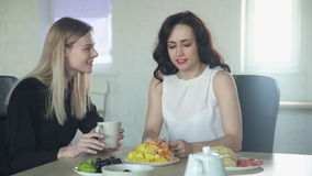 Two women at a table talking with delight and drink from a cup. Beautiful European lady sitting and actively communicate with each other by using body language stock video