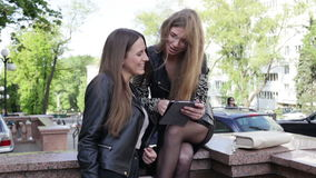 Two women with a tablet. Two young women in the city are looking at the screen of a tablet, touching the screen and smiling stock footage