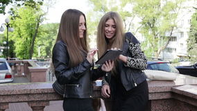 Two women with a tablet. Two young women in the city are passing the tablet to one another, touching the screen and smiling stock video