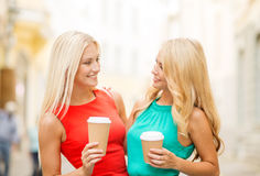 Two women with takeaway coffee cups in the city Royalty Free Stock Images