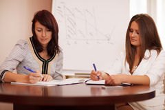 Two women taking notes at a business presentation Stock Photography