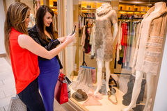 Two women taking a photo of a dress in window display. In mall Royalty Free Stock Photography