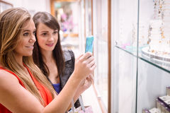 Two women taking a photo of shop display Stock Photo