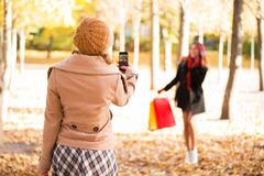 Two women taking photos in the autumn after shopping Stock Photography