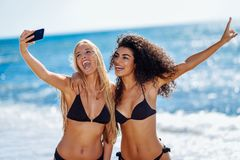 Two women taking selfie photograph with smartphone in the beach. Two young women taking selfie photograph with smart phone in swimwear on a tropical beach. Funny stock photos