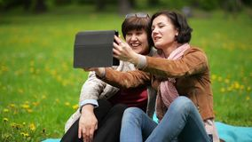 Two Women are Taking Selfie Sitting on Green Grass in the Park. Adult Brunette Daughter and Her Pretty Mother are Using. Tablet Outside, HD stock video footage