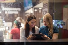 Two women talk cheerfully in the restaurant using Stock Images