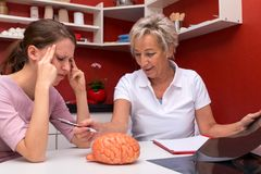 Two women talking abaut brain diseases. One of them is a nurse or doctor, the other have headaches Stock Images