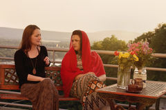 Two Women Talking at Balcony in Sunset Stock Image