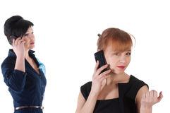 Two women talking by cell phones and smiling. Isolated on white background Stock Photos