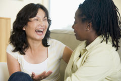 Two women talking in living room and smiling Stock Photo
