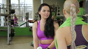 Two women are talking in modern sports club indoors. Blonde and brunette speaking with friendly smiles in gym room. Fitness ladies discuss strength training stock video footage