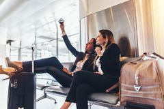 Two women talking selfie while waiting for a delay flight sitting with suitcases in airport terminal.  Stock Photos