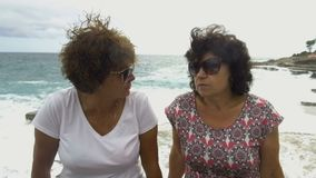 Two women talking while sitting in harbour by sea. Against the background of the waves crashing against the stone pier stock video footage