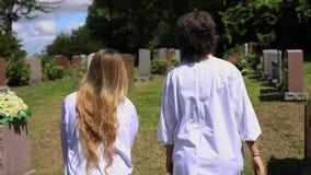 Two women talking while walking in graveyard