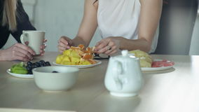 Two women talking at a white table with fruit and drink tea. The brunette in a light blouse broke off slices of mandarin. The blonde in a black dress holding a stock footage