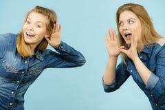 Two women telling tales, rumors gossip stock photo