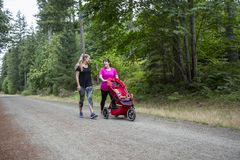 Two women walking and talking together on a trail with a baby stroller stock photography
