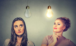 Two women thinking looking up at light bulbs. Stock Photo