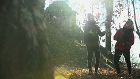 Two women throw leaves into the air shot from a far in slow motion stock footage