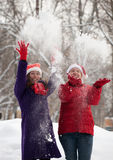 Two  women throw up snow Stock Photo