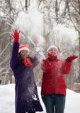 Two  women throw up snow Stock Photo