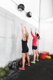 Two women throws medicine balls in fitness gym Royalty Free Stock Photos