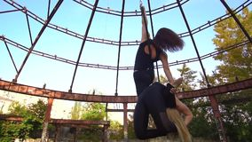 Blonde and brunette hold on to each other and are told in the ring for aerial acrobatics. Two women in tight clothes are engaged in aerial acrobatics in nature stock footage