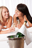 Two women toasting with champagne in bedroom Royalty Free Stock Images