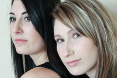 Two women together. Portrait of two beautiful women standing together while one looks away Royalty Free Stock Photos