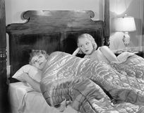 Two women together in bed under a blanket. (All persons depicted are no longer living and no estate exists. Supplier grants that there will be no model release Royalty Free Stock Images