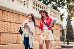 Two women tourists having fun going sightseeing using map in Odessa. Happy friends travelers laughing while walking royalty free stock photos