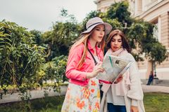 Two women tourists searching for right way using map in Odessa. Happy friends travelers going sightseeing. Together stock photo