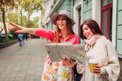 Two women tourists searching for right way using map in Odessa. Happy friends travelers showing direction. And laughing stock images